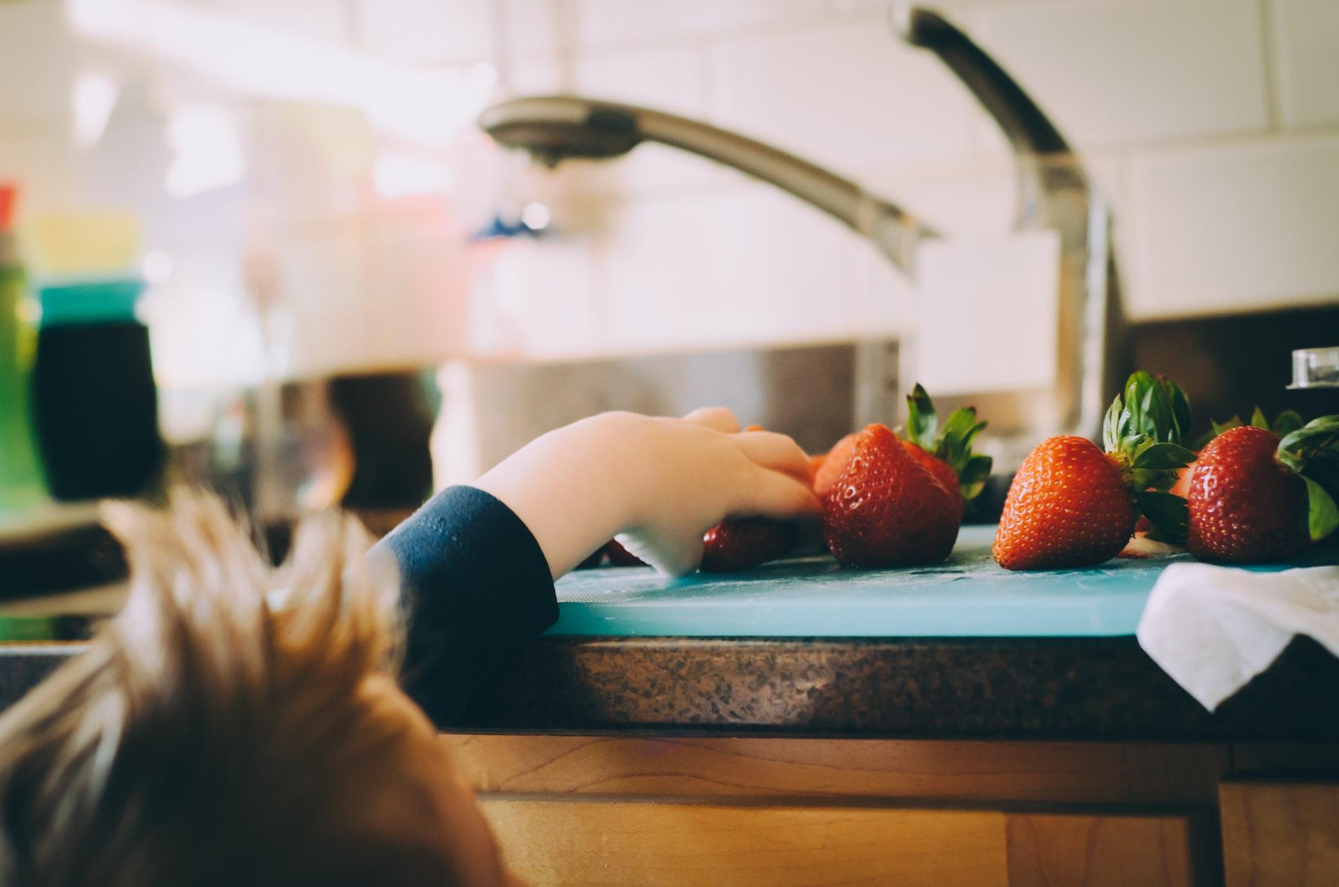 Chłopiec sięga po truskawki