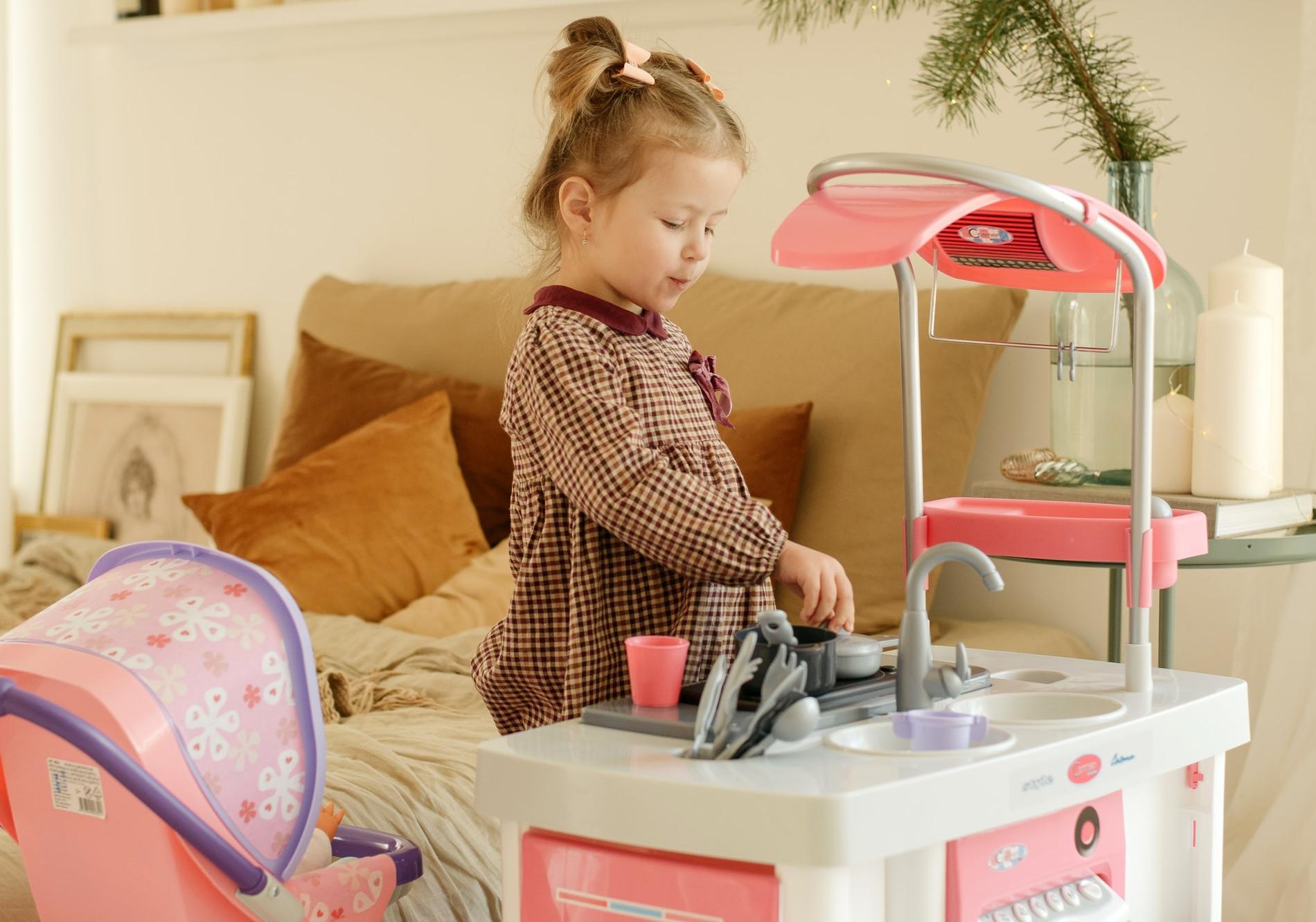 Dziewczynka bawi się zabawkową kuchnią