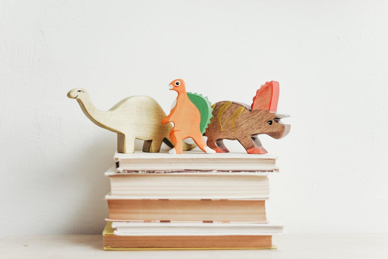 Dinozaury zabawki stoją na książkach
