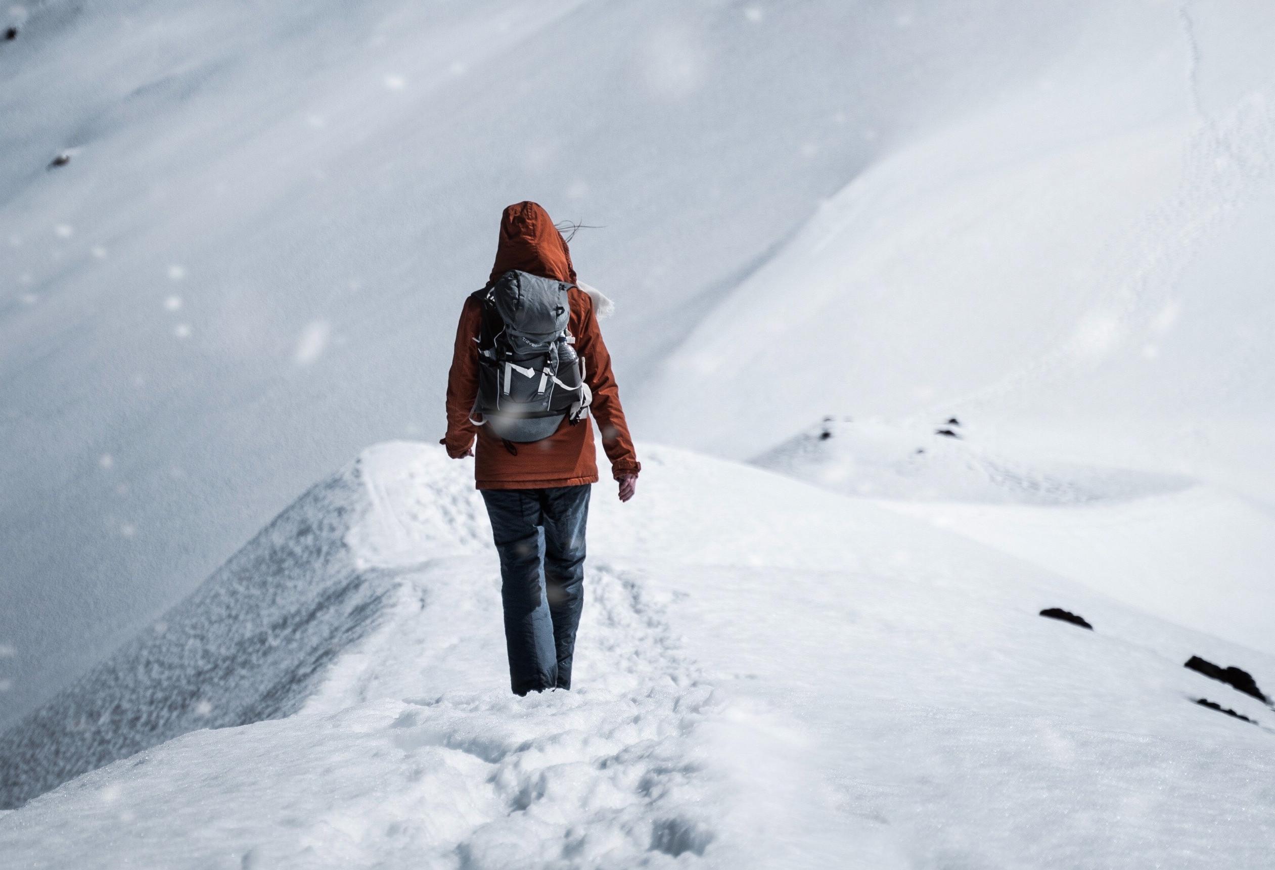 Kobieta spacerująca po śniegu w górach