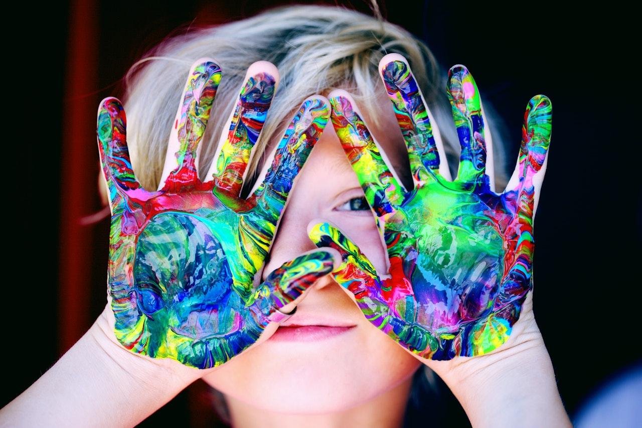 Dziecko z kolorową farbą na dłoniach
