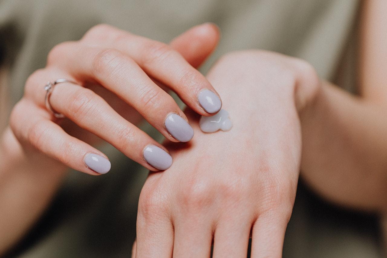 kobieta kremuje ręce