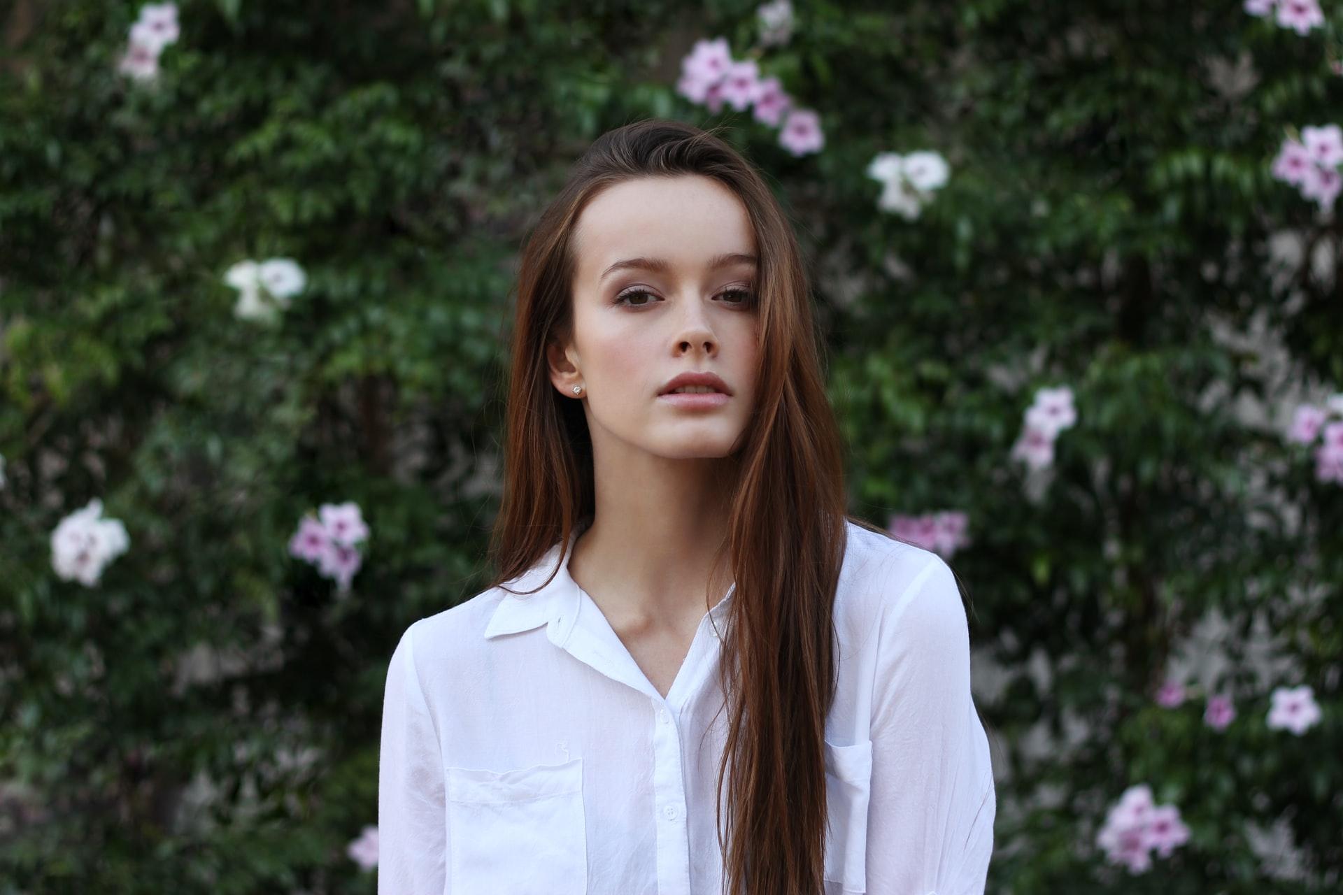 Kobieta w białej koszuli na tle roślin