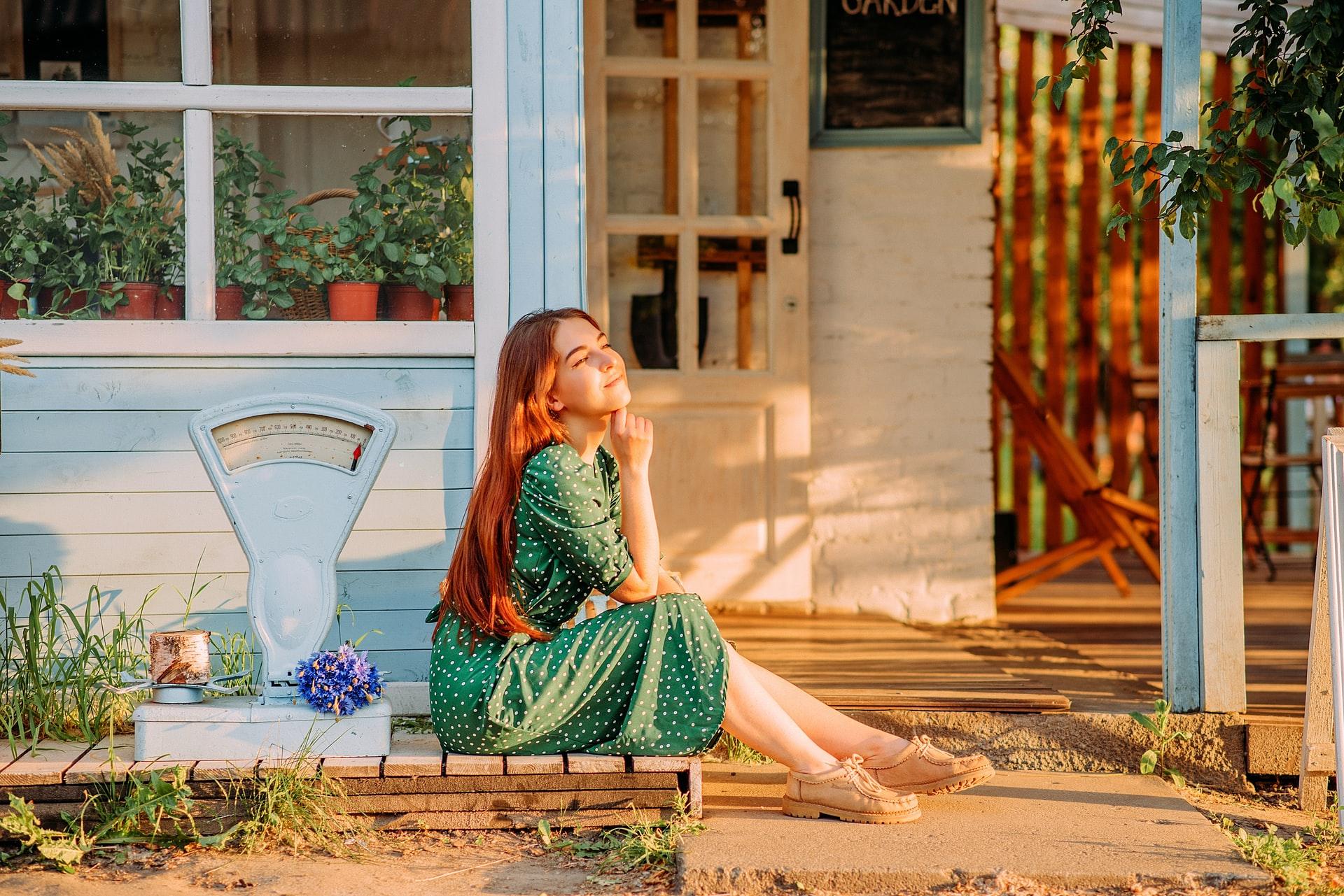 Kobieta siedząca przed domem