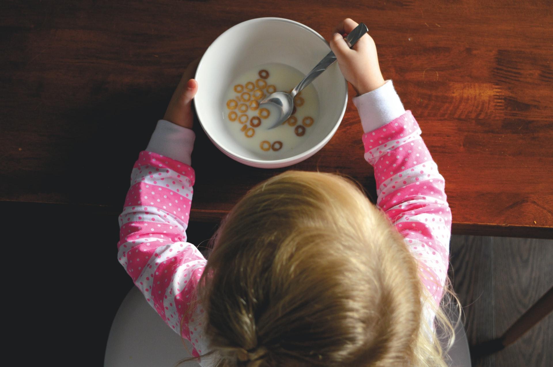 Dziewczynka je płatki z mlekiem